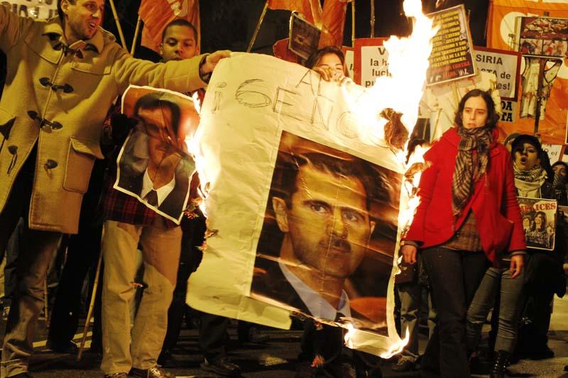 Argentina: un cartel con el rostro del genocida Al Asad arde mientras los manifestantes cantan consignas contra su régimen