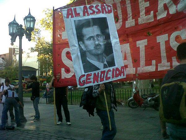 Pancartas contra el dictador genocida de Siria Bashar Al Assad en el acto en Córdoba, Argentina