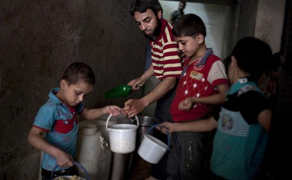 Varios niños recogen la comida dada por una organización benéfica en el barrio de Bustan al-Qaser. J.M. LÓPEZ