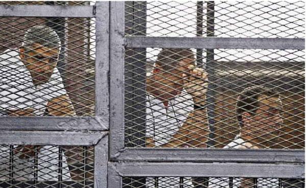 """""""Juro que pagarán por esto"""", exclamó enfadado Fahmy desde la celda de los acusados, después de que se anunciaran las condenas. Greste alzó el puño."""