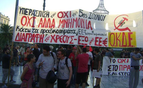 Frente a la bandera de la organización OKDE, en Atenas, en la movilización frente al Parlamento del 22/7, Esther Alcazar de LI de Estado Español y Sedat de IDP de Turquia, junto a un dirigente de OKDE. La bandera dice Defendamos el No del 5 de Julio. No al nuevo Memorando. Contra el crimen de estado de la UE-Tsipras.Cancelacion de la Deuda, Fuera UE y el Euro.